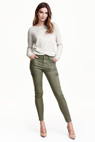 Pantalón cargo: Pantalón cargo en sarga lavada y elástica de algodón con perneras ceñidas. Bolsillos al bies, bolsillos traseros y bolsillos en las perneras con cremallera. Costuras en las perneras y cremallera en los bajos. Cintura estándar.