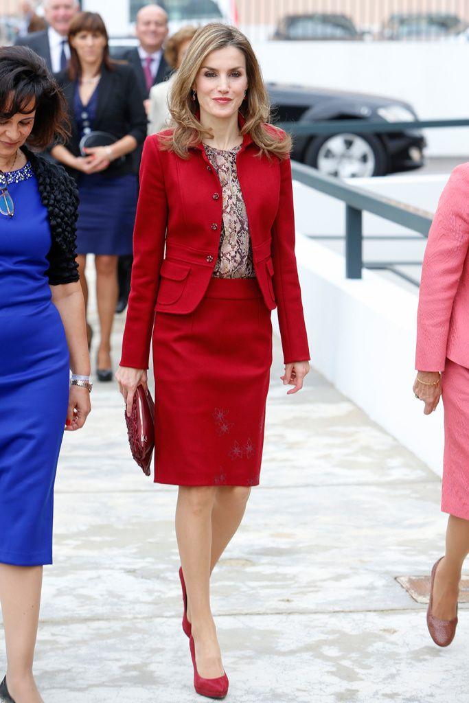 Para su segundo viaje al extranjero en solitario, la reina de España, Letizia, ha escogido un conjunto de chaqueta y falda con discretos bordados florales, clutch, zapatos y pendientes rojos. Rompiendo la monocromía, una blusa con estampado de serpiente. Lisboa, noviembre 2014.