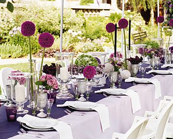 Sleek white plates sit on pewter chargers, and clear hurricanes share space with purple glass votives.