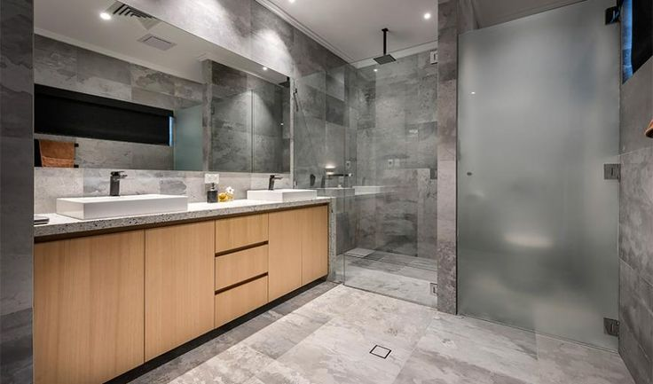 Featuring blemished floor-to-wall grey-tiling, a timber wall-hung vanity, matte-black Mizu Bloc overhead shower and accessories, there's a bold industrial edge encompassing the space. Designed and Built by Swell Homes in East Fremantle WA.