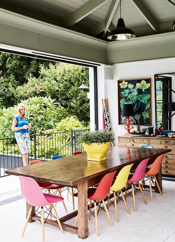 Ким Стефен, хозяйка идекоратор дома в Кейптауне, на террасе. Стол местного производства, разноцветные стулья, Vitra.