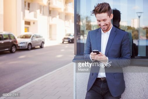Stock Photo : Young businessman using mobile phone against wall by sidewalk