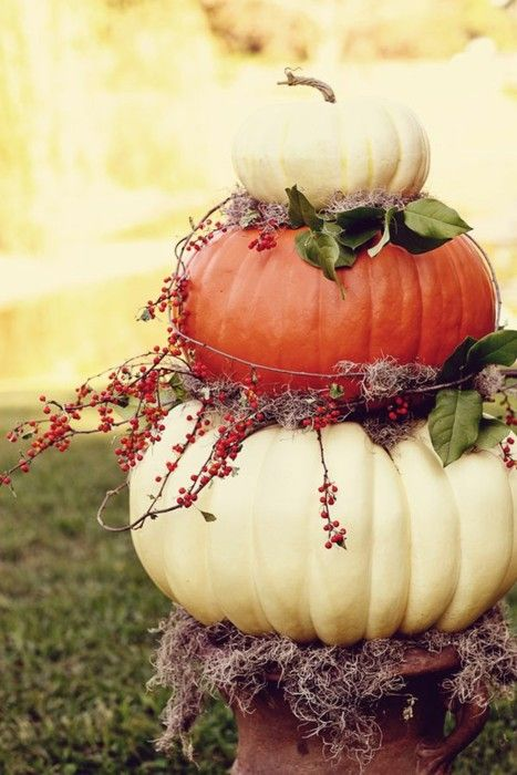 Halloween: Layers of pumpkins with berries and moss stacked on urn.