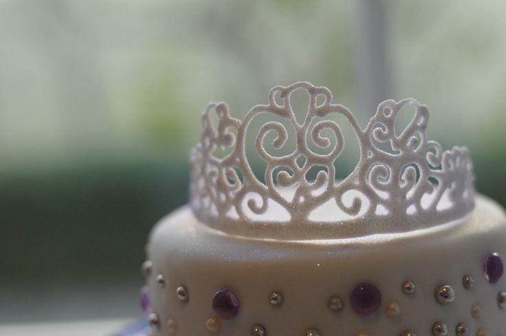 A hand- made royal icing tiara cake topper.