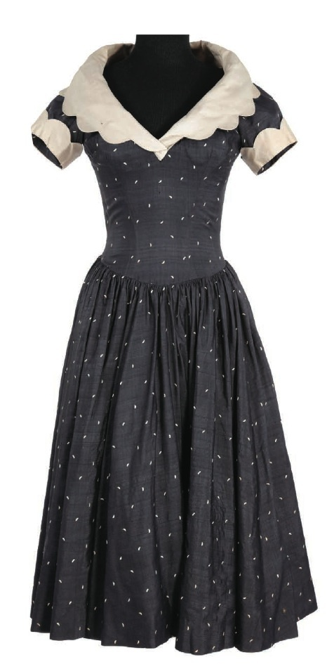 """Charcoal Grey dress. Worn by Ann Miller in """"Kiss Me Kate."""" (1953) Designed by Walter Plunkett. Charcoal grey silk dress with ivory polka dots and collar. Worn by Ann Miller as """"Lois Lane 'Bianca' in the """"Why Can't You Behave""""   number."""