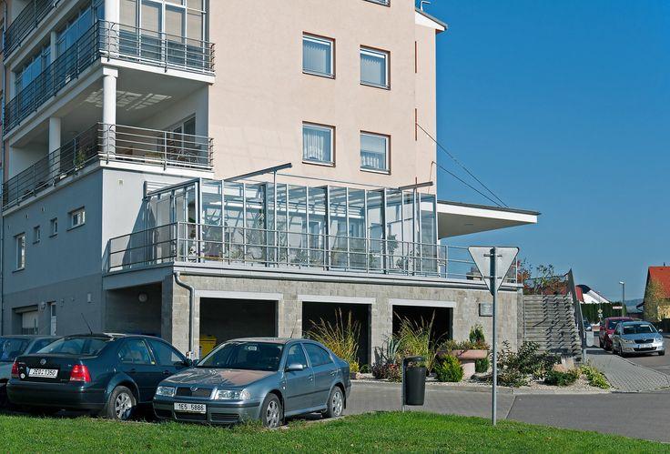 Posuvné zastřešení terasy systémem CORSO GLASS vystavěné na vyvýšené terase.