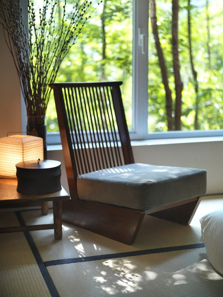 a modern version of a classic Chinese low seat is situated windowside