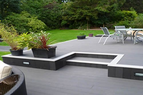 A platform deck designed and built with a subtle level change blends the yard and deck into one outdoor living space.