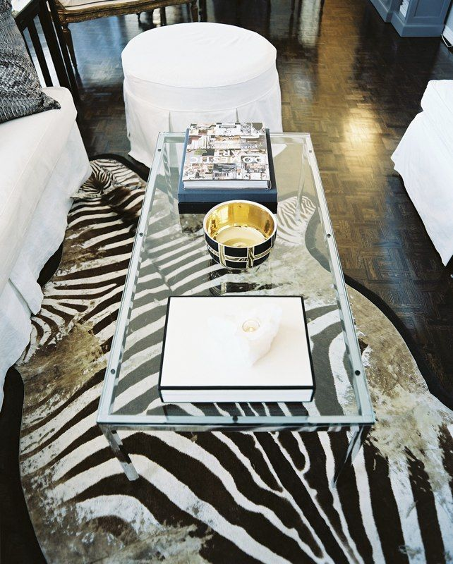 eclectic traditional living room a glasstopped coffee table atop a zebrahide rug