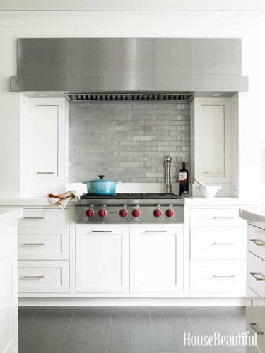 Custom hood extends beyond the span of the 36-inch Wolf cooktop for