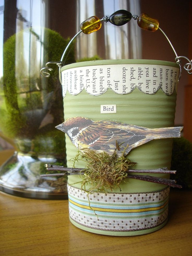 INSPIRATION: Use a recycled can, paint layers of different acrylic paint and embellished with ribbon, vintage paper from a bird book, image of bird, twigs, moss, vintage button, rusty mesh, beades, and wire. Seal with a matte finish.