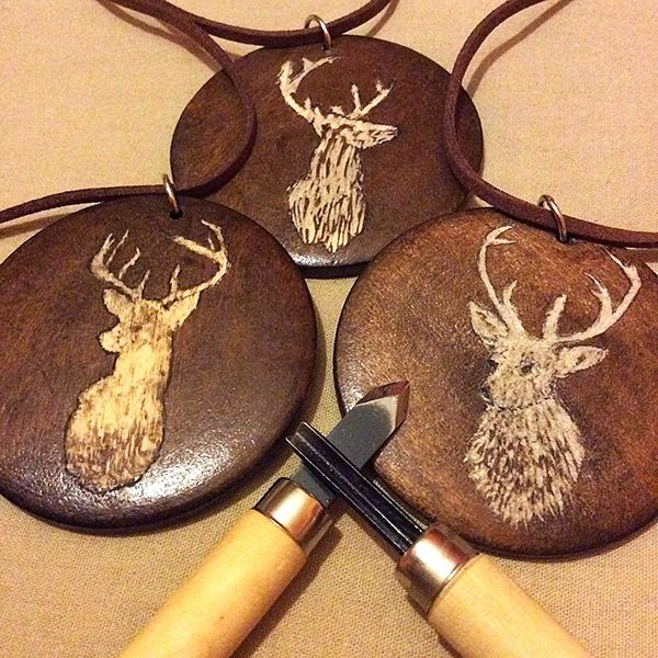 """Handmade pendants, carved and burned on wood. Inspired by my stag heraldry within the game """"Banner Saga 2"""""""
