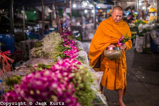 BANGKOK, THAILAND:  A Buddhist monk walks through the Bangkok Flower Market on his morning rounds collecting alms. The Bangkok Flower Market (Pak Klong Talad) is the biggest wholesale and retail fresh flower market in Bangkok.  The market is busiest between 3:30AM and 6AM.      PHOTO BY JACK KURTZ