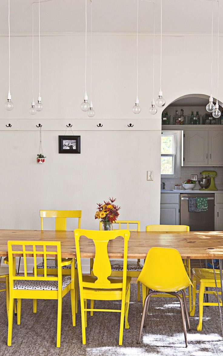 Love everything about this room...white walls, bright yellow mismatched chairs, DIY wood table, light fixtures, and the hooks all the way around the room are genius!