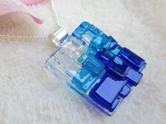 Este hermoso colgante de cristal del arte es fundido de piezas azul oscuro. vidrio en la base transparente con algunos travesaños azul en él claro
