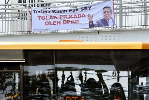 Thank you! A TransJakarta bus passes beneath a banner with a photo of President Susilo Bambang Yudhoyono at Manggarai bus terminal in Jakarta on Monday. The banner was an expression of ... #HakamNaja2014