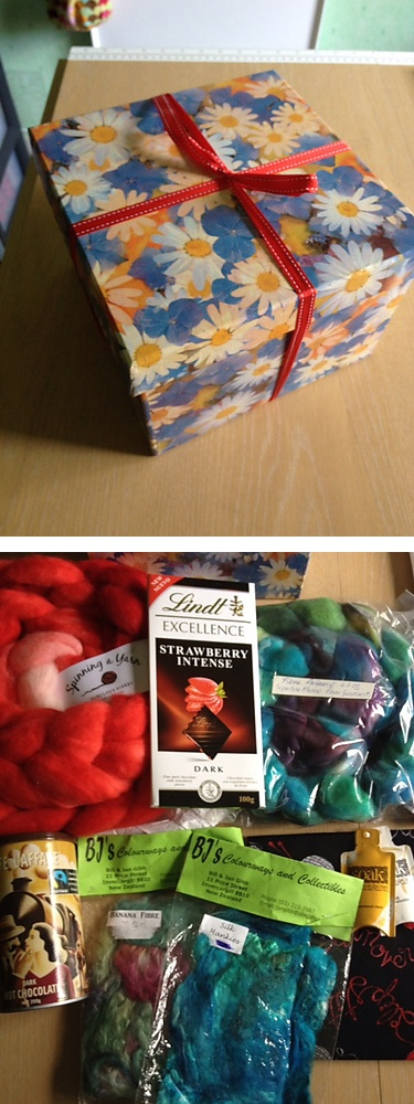 """kiltsnquilts from sues153: """"Two lovely lots of fibre…..a beautiful bright red to orange gradient from Spinning a Yarn and a lovely Paua coloured braid from Artemis Fibres. There was also a silk hankie and a bag of banana fibre, some divine Strawberry Lindt chocolate, some dark hot chocolate , a piece of knitting fabric for a project bag and some Soak."""""""