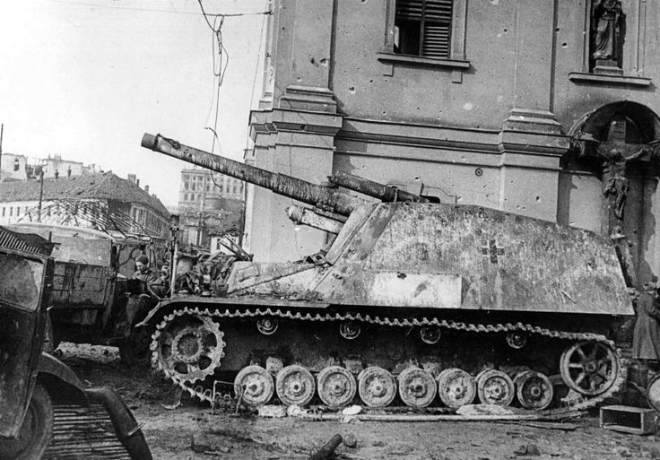 """Abandoned or destroyed German 150-mm self-propelled howitzer """"Hummel"""" (Sd.Kfz.165 Panzerhaubitze Hummel) in Budapest after the storming of the city by Soviet troops. Dotted with marks from bullets and shells wall of the building for SAU — evidence of the ferocity of the occurring battle for the city."""