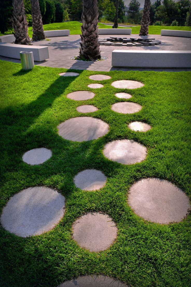 10 Landscaping Ideas For Using Stepping Stones In Your Garden // These round stepping stones surrounded by grass connect the various areas of this park, and add a touch of fun with their circular shapes.