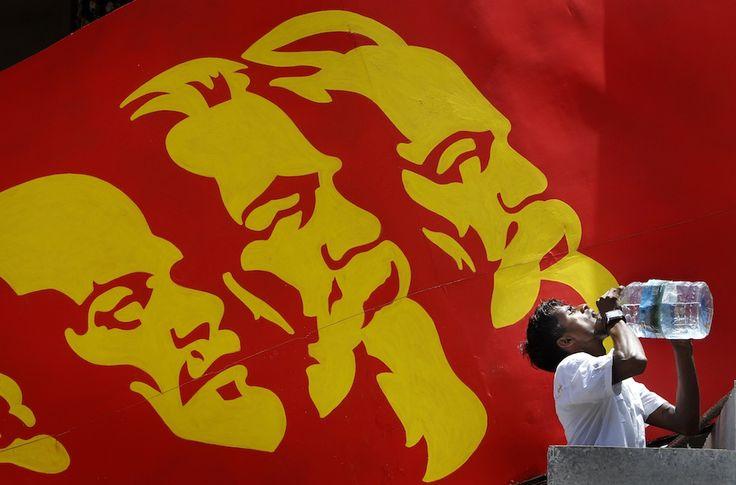 Colombo, Sri Lanka    Un attivista del Partito comunista dello Sri Lanka durante una marcia per il Primo Maggio. Alle sue spalle un manifesto con i ritratti di Vladimir Lenin, Karl Marx e Friedrich Engels. (AP Photo/Gemunu Amarasinghe)
