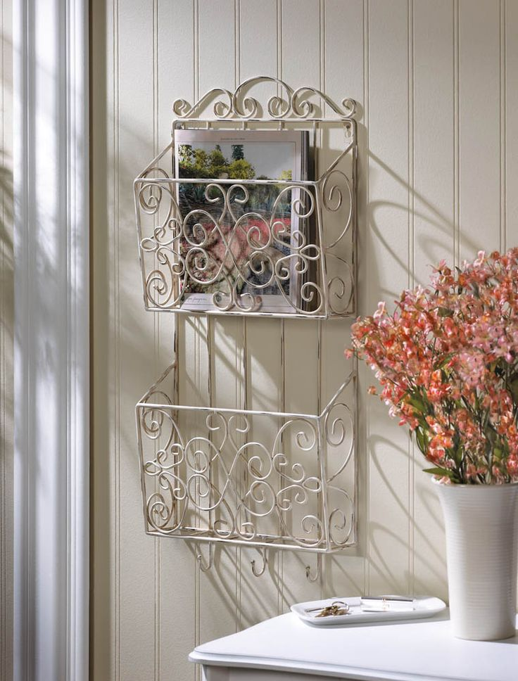 Double the pretty storage on your wall with this magazine wall rack. The weathered white finish of this scrolling design features two racks for magazines, papers, tablets and more. Below, you'll find three small hooks to keep you organized.