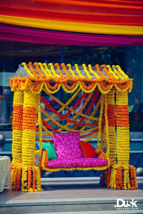 Real Indian Weddings - Divya and Dhiraj | WedMeGood | Orange and Yellow Genda Flower Swing for a Mehendi Function Picture Courtesy: DotDusk Studios #wedmegood #realwedding #genda #flowers