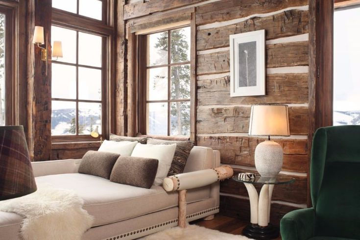 One of the best rustic master bedroom ideas we've seen this year, and it features a green armchair, a sleek grey sofa-bed, and the charming worn wooden planks.