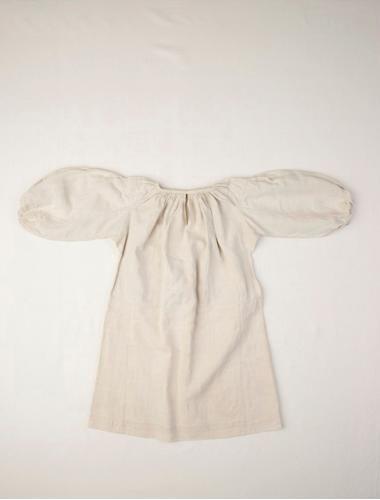 """Naisen paita, sekä alaset että yliset käsinkudottua pellavapalttinaa. Käsin ommeltu, ainoastaan kaula-aukon reunus ja olkapääsaumat on ommeltu koneella. Kaula-aukko ja hihansuut on poimutettu, kaula-aukkoon on ommeltu reunus, """"linninki"""", mikä puuttuu jo hihansuista. Pienet napit ja lenkit kuuluivat kaula-aukkoon. Suomalais-ugrilaiset kokoelmat Jan Lindroth 2011"""