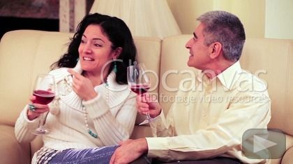 Video of a happy loving mature couple drinking a glass of red wine, joking and laughing on the sofa of their living room. HD Stock Footage Clip. Medium shot. 2015-02-01.
