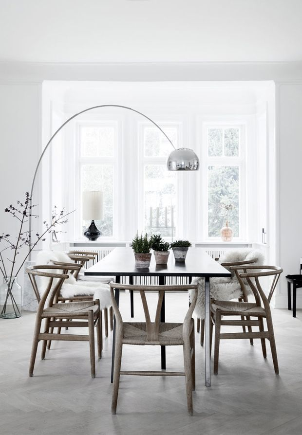 Dining: Hans Wegner wishbone chairs, arco lamp, pale grey herringbone wooden floor, bay window, decorative branches in glass vase