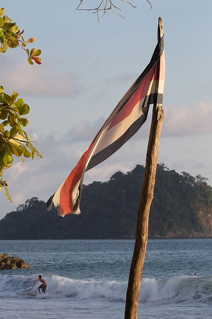 Costa Rican Flag  and Surfer on Manuel Antonio Beach looking towards the National Park. Photography by John Williamson
