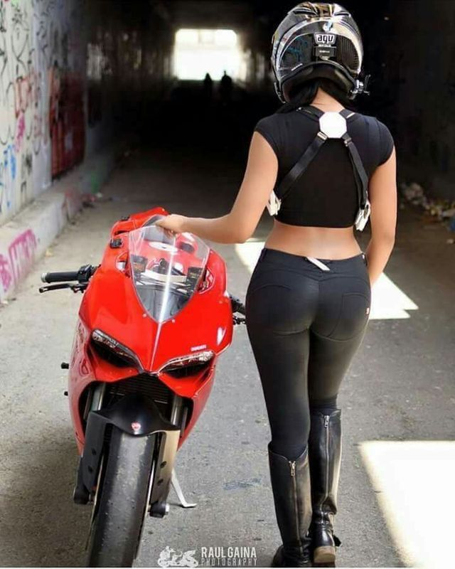 Female Motorcyclist Dressed Black Leather Outfit And Leggins Sitting On Bike Seat, Looking Behind, View