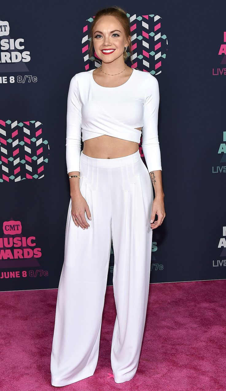 DANIELLE BRADBERY in a white criss-cross crop top and coordinating wide-leg trousers accessorized with a gold choker and a red lip for a pop of color.