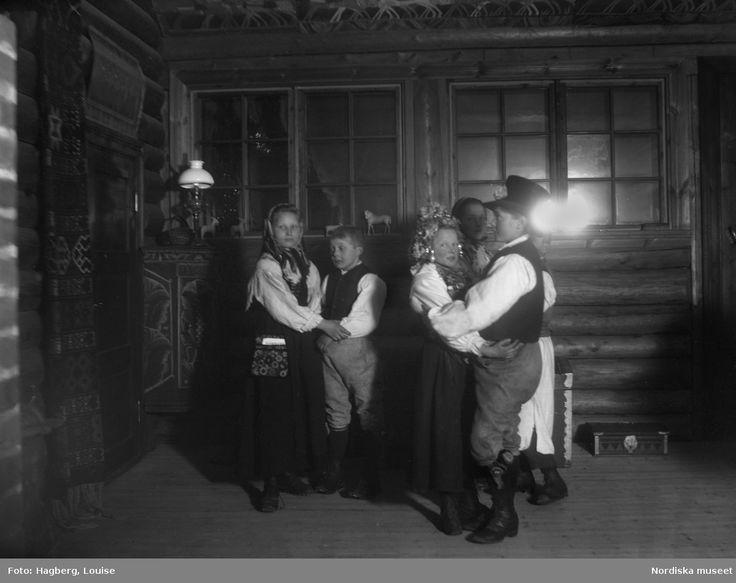 """Mats-firande med Brud och brudgum"""" i Gagnef. Tre pojkar och tre flickor klädda i folkdräkt står parvis uppställda och håller varandras händer."""