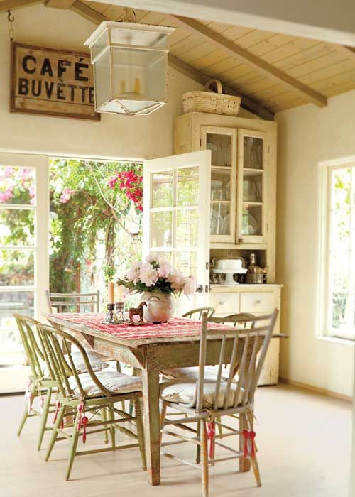 Mismatched chairs surround a worn wood dining table giving the space lived-in charm.