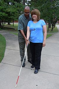Keep Rockin' Around Your Tree by Improving Your Orientation and Mobility Skills as an Individual Who is Blind or Visually Impaired (Image: male orientation and mobility instructor shows a woman how to use her white cane)