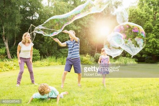 Stock Photo : Family playing with large bubbles in backyard