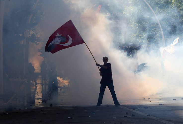 Tear gas surrounds a protestor holding a Turkish flag with a portrait of the founder of modern Turkey, Mustafa Kemal Ataturk, as he takes part in protests against the Turkish Prime Minister and his ruling Justice and Development Party (AKP) in Ankara on June 1, 2013. (Adem Altan/AFP)