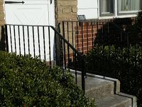 ornamental wrought iron railing, metal railing, iron, wrought iron railing at front entrance way on stairs