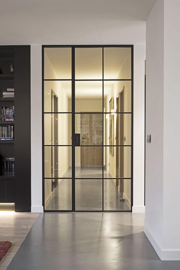 Hoge zwart gelakte metalen deur met vast zijpaneel in glas