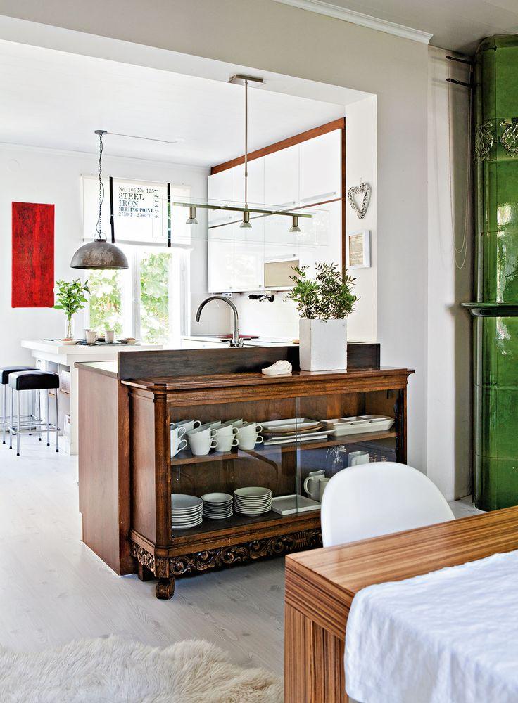 Keittiö suunniteltiin ja asennettiin itse. Perityt ja uudet säilytyskalusteet viihtyvät selätysten. Mummin vitriinissä säilytetään astioita. Kiiltävät keittiönkaapit ovat Kalustetukusta ja vetimet Ikeasta. Kolmespottinen valaisin tiskipöydän yllä on K-Raudasta.