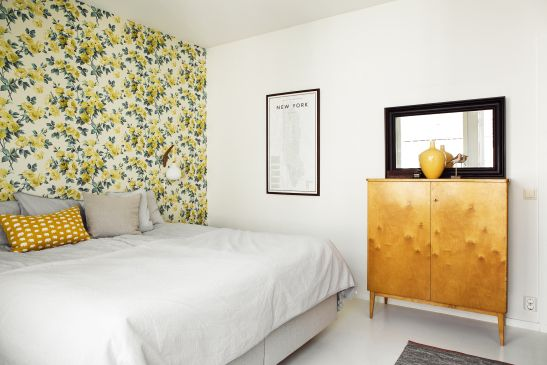 White bedroom given a splash of colour with a floral wallpaper on one wall, yellow throw pillows and a wooden vintage cabinet