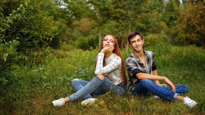 Couple teens sitting on the lawn by Elena Vagengeim on @creativemarket