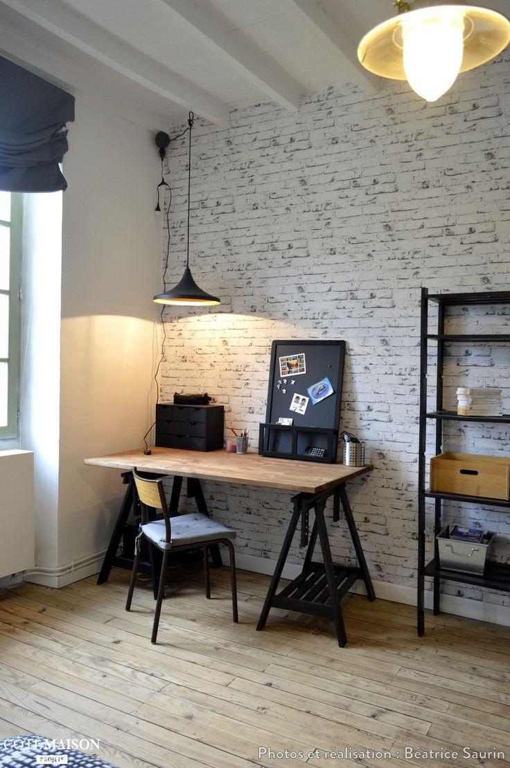 Coin bureau avec poutres apparentes repeintes en blanc et papier peint façon mur de briques.