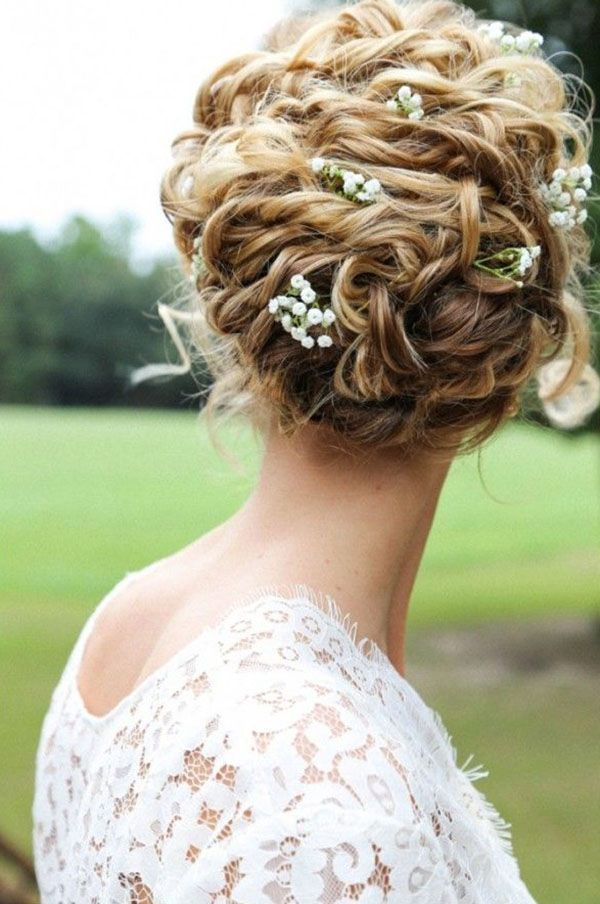 soft updo with flowers for naturally curly hair http://weddingwonderland.it/2015/06/15-acconciature-per-le-spose-dai-capelli-ricci-naturali.html