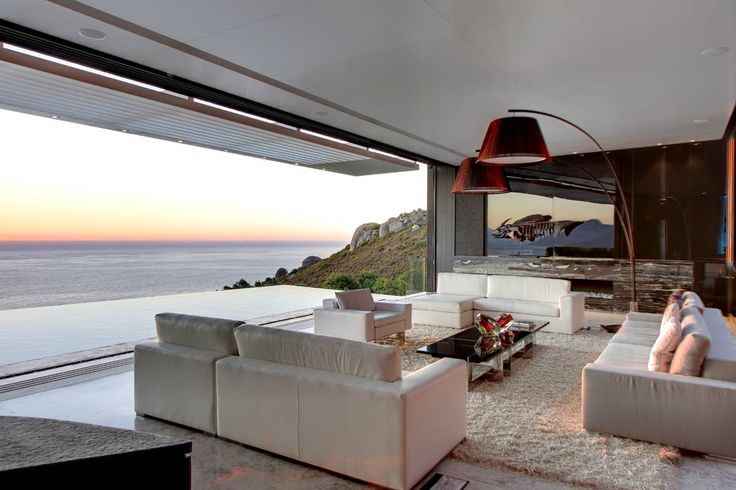 white leather couches, shaggy carpet, views, rim flow pool, marble floors, glass coffee table, wall art
