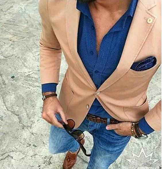 A smart casual combination of a tan coat and blue skinny jeans can maintain its relevance in many different circumstances. Add brown leather tassel loafers to your look for an instant style upgrade.   Shop this look on Lookastic: https://lookastic.com/men/looks/blazer-dress-shirt-skinny-jeans/24004   — Blue Dress Shirt  — Tan Blazer  — Navy Paisley Pocket Square  — Dark Brown Bracelet  — Dark Brown Woven Leather Belt  — Dark Brown Leather Watch  — Dark Brown Sunglasses  — Blue
