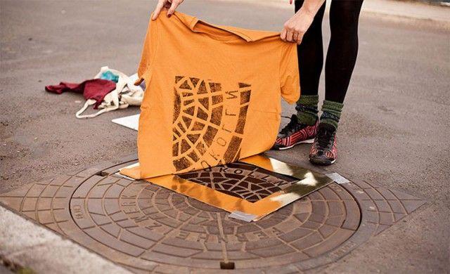 Художники используют крышки люков для печати на сувенирных футболках