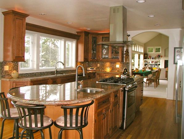 Angle wall cabinet and adjacent straight cabinets are fitted with leaded glass inserts, custom art that enhances the inset maple cabinets' traditional style