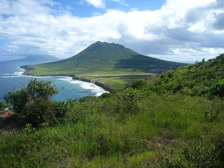 View looking southeast along the Atlantic coast, showing the airport runway in the middle distance, Lynch Beach beyond that, then the Quill, St. Eustatius' dormant volcano, and over the water in the distance, the northern end of the island of St. Kitts.